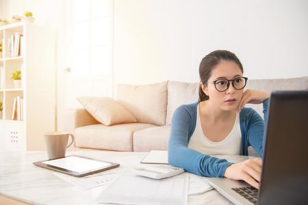 かなりアジアの女性は、自宅のリビング ルームでソファの上に座って計画新年のための法案をチェックのラップトップ コンピューターを使用して。
