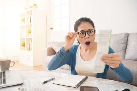 Stressed young mixed race asian woman is panicking checking bills, taxes and bank account balance sitting on sofa in the living room at home. interior and domestic housework concept.
