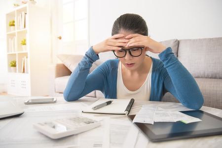 beauty asian stressed worried young woman is doing banking and administrative work holding bills at home sitting on sofa in the living room at home. interior and domestic housework concept.