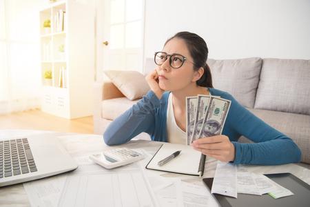 De aantrekkelijke jonge gemengde ras Aziatische vrouw die aan financiën werken maakte zich over de uitgaven van uitgavenkosten thuis op bank in de woonkamer ongerust. interieur en huishoudelijk werk concept.