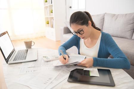 노트북 및 디지털 테이블 터치 패드를 사용 하여 가정에서 거실에서 소파에 앉아 청구서를 계산하는 아름 다운 아시아 중국 여자. 내부 및 국내 집안일