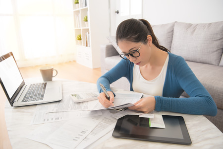 beautiful asian chinese woman using laptop and digital table touch pad to calculate bills sitting on sofa in the living room at home. interior and domestic housework concept. Archivio Fotografico