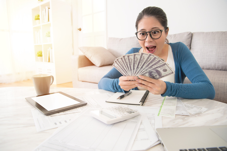 portrait of happy excited successful young business woman holding money dollar bills and looking at cash feel surprised sitting at living room. Positive emotion facial expression feeling. Stockfoto