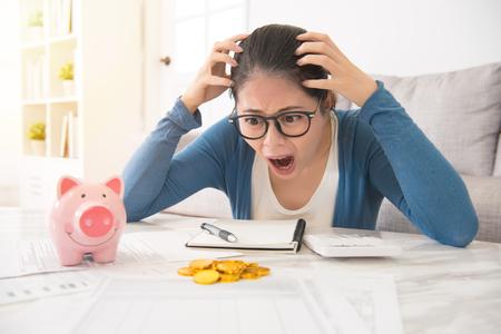 gekke Aziatische huisvrouw voelt zich gek om te zien dat minder geld uit het spaarvarken komt, niet genoeg om uitgaven te betalen zittend op de bank in de woonkamer thuis. interieur en huishoudelijk werk.