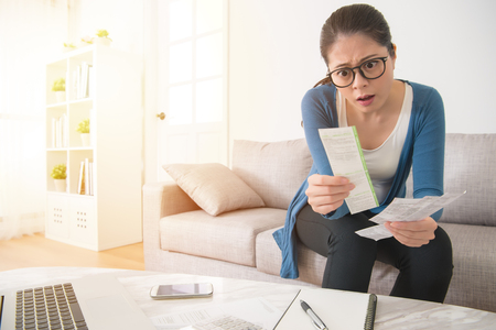beautiful girl stressed over bills. surprised young woman using computer and holding bill and bank statements sitting on sofa in the living room at home. interior and domestic housework concept.