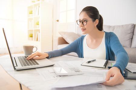 Gelukkige jonge gemengde ras Aziatische Chinese vrouw het berekenen rekeningen door laptop computerzitting op bank in de woonkamer thuis. interieur en huishoudelijk werk concept. Stockfoto