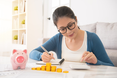 smile mixed race asian chinese house woman counting her savings from piggy bank money tower sitting on sofa in the living room at home. indoors interior and domestic housework. 写真素材