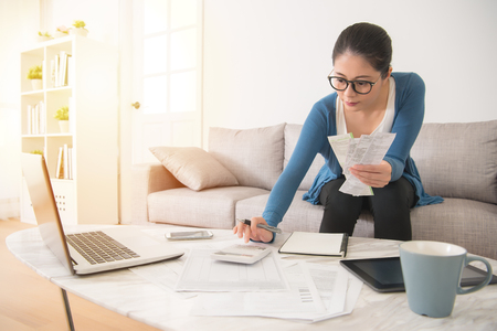 mixed race asian chinese housewife calculating accounting new year budget holding a receipt using calculator sitting on sofa in the living room at home 스톡 콘텐츠