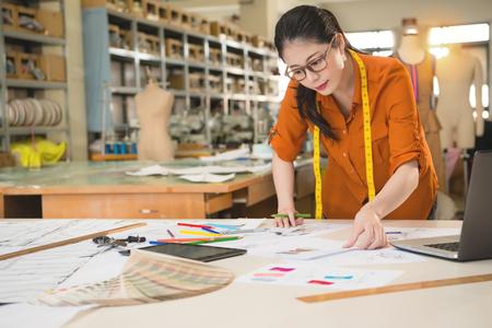 Bela escolha de designer de moda feminina procurando o melhor esboço de design de mercado de correspondência com amostra de tecido no estúdio de escritório de fabricação. profissão e conceito de ocupação do trabalho.