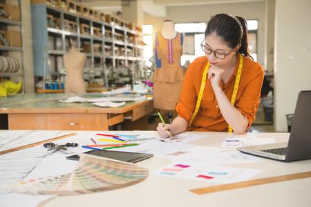아시아 패션 여자의 정통 이미지 디자이너 드로잉 디자인 스케치 그녀의 제조 사무실 스튜디오에서 일하고. 직업 및 직업 직업 개념.