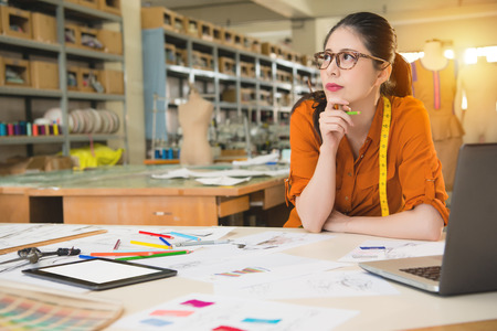 fashion woman designer looking away thinking of designs sketch on tablet computer in manufacturing office studio. profession and job occupation concept.