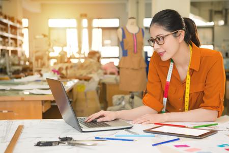 Joven belleza feliz joven diseñador de moda asiática utilizando ordenador portátil de investigación en Internet para la temporada nueva tendencia en la fabricación de estudio de oficina. Profesión y trabajo concepto de ocupación. Foto de archivo - 80560579