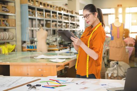 Zelfverzekerde succesvolle mode-chinese vrouw ontwerper permanent en met behulp van digitale tafel touch pad voor onderzoek in de productie kantoor studio. Beroep en baan beroep concept. Stockfoto