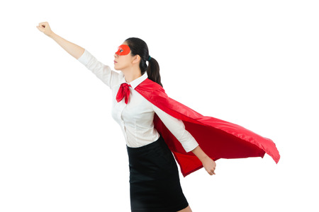 superhero business woman flying with red hero goggles cape clothing gesture fist ready take off above the white copyspace wall background over blank area concept. Foto de archivo