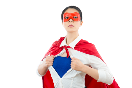 beautiful businesswoman acting like a superhero and tearing her shirt off showing hero blue clothing with copyspace on the white wall background with red goggles and cape. Banco de Imagens