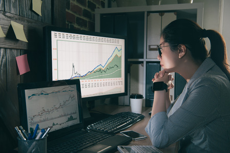 chinese trustworthy analysts focused on her work and thinking about stock dynamics. Portrait of a female sitting watching her computer in a office. Banque d'images