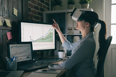 smiling office woman getting experience using VR headset glasses at company with gesticulating. asian girl pointing touch air by virtual reality.