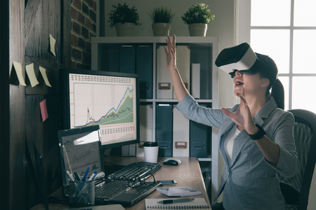 simulations: asia trading manager organize workflow by virtual reality. Person wearing VR headset interact with financial graph with stock market on air.