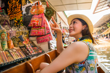 Travel tourist happy woman sitting on river boat. Girl on summer vacation visiting famous tourist destination having fun smiling pointing market product. Asia holiday and travel vacation concept