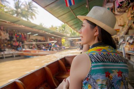saduak: Damnoen Saduak floating market of Thailand. Tourist on Asia travel looking at Thai landscape sitting on famous tourist destination and attraction. Woman traveler on Asia travel vacation Stock Photo