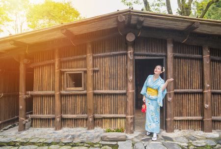 Beauty girl wearing traditional kimono in front of old wooden house. Japaneses enjoying sunshine after rain, asian woman looking up at clearing sky checking if its raining during traveling on japan Stok Fotoğraf