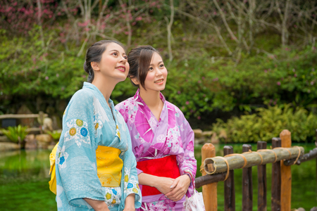 Girlfriends. Happy asian girls portrait of smiling friends having fun together on sightseeing cherry blossom on antique bridge enjoying travel. Beauty young japanese women wearing traditional kimono. Stock Photo
