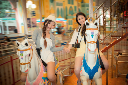 happy sister happy friends on the carousel and hand in hand each other taking the picture together commemorate their summer holiday travel in amusement park. vintage retro film color.