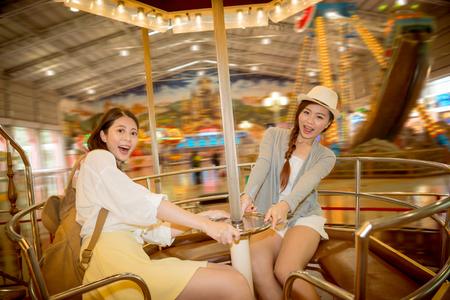 Mujeres excitadas asiáticas que se sientan juntas en el juego de la taza de café y que agarren el volante rápido que gira en el parque de atracciones en días de fiesta de vacaciones con los amigos sobre color retro de la película del vintage. Foto de archivo - 81084121