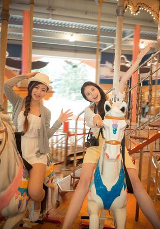 Les jolies filles asiatiques vont au parc d'attraction en jouant des installations récréatives de manège en fêtant des festivals heureux de prendre des photos pour commémorer les vacances. Vintage rétro couleur de film. Banque d'images - 81084134