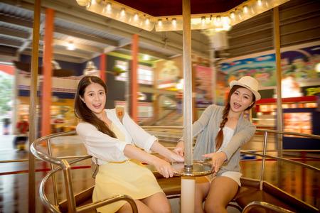 楽しむレジャー ステアリング ホイールをつかんで高速回転椅子カップを再生休暇の時に遊園地に行くアジアの中国人留学生は、ヴィンテージのレトロなフィルム ・ カラーの性能刺激を表示します。 写真素材 - 81084133