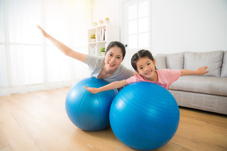 young mixed race asian chinese mother and her daughter lying on the big softness ball and opening hands as flying cheerful doing yoga exercise at home. Banco de Imagens - 81427040