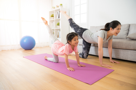 asian pretty mother and her youth kid daughter in the gym center doing stretching fitness exercise yoga together, parent accompany children sport concept.