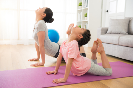 asian mother and daughter doing yoga exercises on vacation in the room at home. people having fun indoors with fitness. concept of friendly family and of summer day. Фото со стока