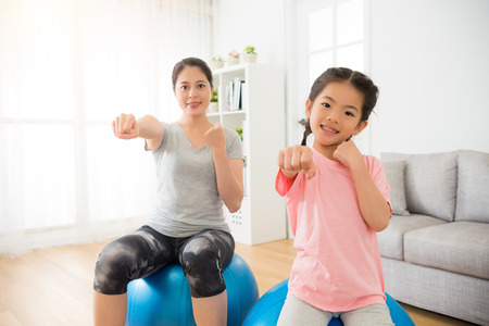 woman and children hands gesture as boxing and hit air with sitting on the fitness ball training balance and strength in the professional yoga class at gym center. Standard-Bild
