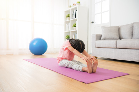 asian little youth girl sitting on the wooden floor with mat straighten her legs and hands catch feet stretch body  with yoga fit sport at home in the room on sunny holiday.