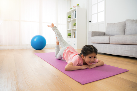 children girl doing yoga gym fitness action alone at home with big blue ball enjoying sporting stretching body lying on the floor in the room on sunny day afternoon. Фото со стока
