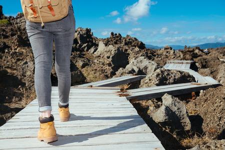夏休みで美しい自然の風景を表示する準備ができている木の板のパス上を歩いて女性トレッカーのクローズ アップ写真。