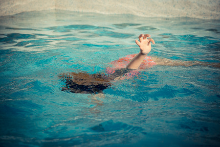 young little girl floating at swimming pool and showing hand calling for help when she playing on summer holiday and drowning in water. Archivio Fotografico