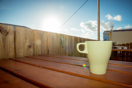 cup of coffee on wood table by country village hotel villa in the afternoon with shiny sunlight refract showing rainbow image. Banco de Imagens