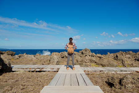 beautiful elegant female hiker standing on path intersection point looking at sea view and enjoying wind in summer vacation.