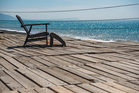 beautiful blue sea view in tropical island and one nobody wooden relaxing chair on vintage style wood board offered travel people to resting sunbathing. Stock Photo - 81459690