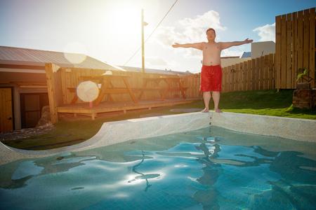 빨간색 반바지를 입고 아시아 남자 수영 풀 옆에 서있는 무기를 열 준비가 여름 휴가에서 물에 뛰어 태양 호텔에서 눈부심.