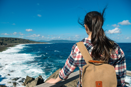 back view photo of pretty beauty woman traveler standing on landscape stage looking at blue sea view and enjoying comfortable wind in summer.