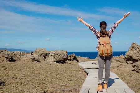 achteraanzicht foto van schoonheid aangenaam backpacker vrouw opening handen gezicht naar zee landschap genieten van natuurlijke wind tijdens tropische reizen.