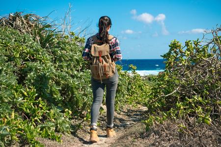 国立公園のハイキング、夏の休暇中に日当たりの良い青い海の風景と風を楽しんでを見て自由レジャー旅行者女性。 写真素材