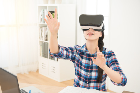 computer simulation: portrait of businesswoman in virtual reality glasses working in her office connect computer work report organize information content with hands in the air. Stock Photo