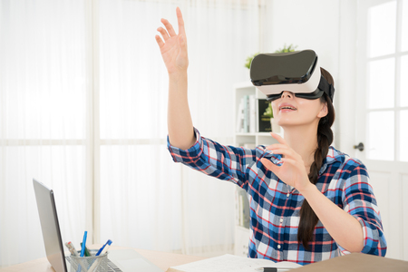 amazed young girl testing virtual reality 3D video glasses VR headset in a office by reality sitting in the studio with curious hands gesticulating moving in th air. Imagens