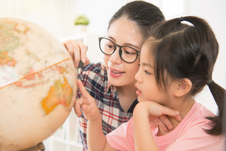 pretty homeschooling mother happy teaching smart daughter private lessons in globe. asia seriously girl children touch map and curious watching.