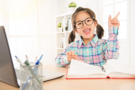 교육 및 행동 학습 개념입니다. 공부 하 고 컴퓨터와 손가락으로 학교에서 책을 읽고 안경에 작은 학생.
