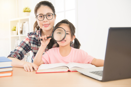 portrait of glasses woman teacher and young girl children studying with magnifier and pc reading. little daughter use glass let eye become bigger.